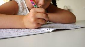 Ο σπουδαστής γράφει με τους αριθμούς και τις επιστολές ballpoint μανδρών στο σχολικό σημειωματάριο απόθεμα βίντεο