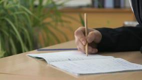 Ο σπουδαστής γράφει το κείμενο στο βιβλίο άσκησης χρησιμοποιώντας το μολύβι απόθεμα βίντεο