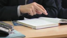Ο σπουδαστής κτυπά τις σελίδες του εγχειριδίου κλείστε επάνω φιλμ μικρού μήκους