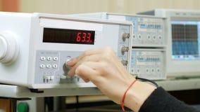 Ο σπουδαστής μηχανικών γυναικών ρυθμίζει την ηλεκτρική γεννήτρια με το χέρι Αλλάζει τους αριθμούς στη συσκευή και προσεκτικά φιλμ μικρού μήκους