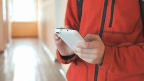Ο σπουδαστής που κρατά ένα άσπρο smartphone στο εσωτερικό απόθεμα βίντεο