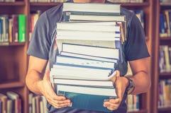 Ο σπουδαστής φέρνει τα βιβλία στη βιβλιοθήκη στοκ εικόνα