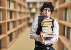Ο σπουδαστής Nerd δανείζεται πολλά βιβλία στη βιβλιοθήκη Στοκ Εικόνες