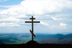 Ο σταυρός πάνω από το βουνό ενάντια στο διαγώνιο ουρανό Ξύλινος σταυρός σε έναν λόφο χριστιανικός σταυρός Στοκ Φωτογραφία