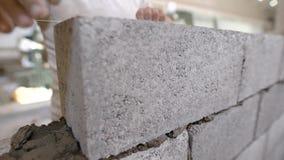 Ο στενός πυροβολισμός στα χέρια πλινθοκτιστών ` s, ο οικοδόμος βάζει τα τούβλα, χρησιμοποιώντας μια τεντωμένη σειρά για ένα ομαλό φιλμ μικρού μήκους