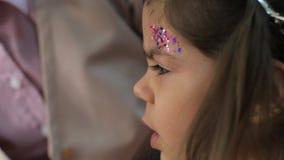 Ο στιλίστας κάνει το επαγγελματικό makeup του μικρού κοριτσιού με τα μοντέρνα σπινθηρίσματα στο brow στο ινστιτούτο καλλονής φιλμ μικρού μήκους