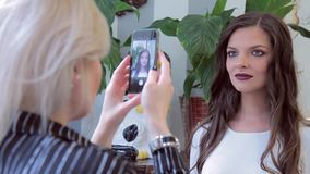 Ο στιλίστας κάνει τη φωτογραφία στο τηλέφωνο με το makeup και την τρίχα, τα οποία έκανε φιλμ μικρού μήκους