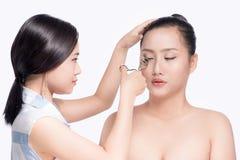 Ο στιλίστας κάνει το επαγγελματικό μάτι makeup Όμορφο ασιατικό μοντέλο Στοκ φωτογραφία με δικαίωμα ελεύθερης χρήσης