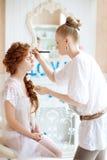 Ο στιλίστας κάνει makeup τη νύφη στη ημέρα γάμου στοκ φωτογραφίες