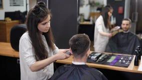 Ο στιλίστας τρίχας επιλέγει το χαμηλότερο μέρος της τρίχας στο κεφάλι προκειμένου να δημιουργηθεί ένα μοντέρνο hairstyle στην ομο φιλμ μικρού μήκους