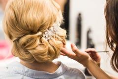 Ο στιλίστας τρίχας κάνει τη νύφη πριν από έναν γάμο στοκ εικόνες με δικαίωμα ελεύθερης χρήσης