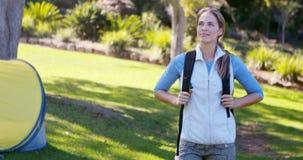 Ο στοχαστικός θηλυκός οδοιπόρος που στέκεται με παραδίδει τις τσέπες φιλμ μικρού μήκους