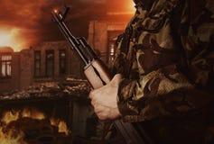 Ο στρατιώτης κρατά το πυροβόλο όπλο στο αποκαλυπτικό υπόβαθρο Στοκ φωτογραφία με δικαίωμα ελεύθερης χρήσης