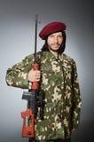 Ο στρατιώτης με το περίστροφο ενάντια σε γκρίζο Στοκ φωτογραφία με δικαίωμα ελεύθερης χρήσης
