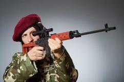 Ο στρατιώτης με το περίστροφο ενάντια σε γκρίζο Στοκ Εικόνες