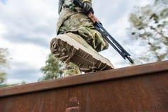 Ο στρατιώτης με το πυροβόλο όπλο διασχίζει τη ράγα Στοκ εικόνα με δικαίωμα ελεύθερης χρήσης