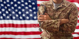 Ο στρατιώτης με το στηθοσκόπιο σε μια αμερικανική στρατιωτική στολή, που στέκεται σε ΗΠΑ σημαιοστολίζει το υπόβαθρο Στοκ Φωτογραφία