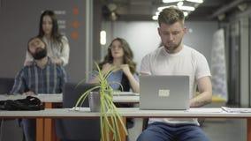 Ο συγκεντρωμένος νεαρός άνδρας στην άσπρη μπλούζα που λειτουργεί με τη συνεδρίαση lap-top στον πίνακα στο σύγχρονο γραφείο απόθεμα βίντεο
