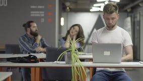 Ο συγκεντρωμένος νεαρός άνδρας στην άσπρη μπλούζα που λειτουργεί με τη συνεδρίαση lap-top στον πίνακα στο σύγχρονο γραφείο φιλμ μικρού μήκους