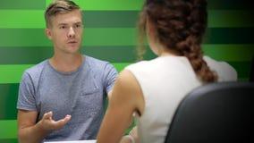 Ο συγκινημένος άνδρας μιλά σε μια γυναίκα, παρουσιάζει τηλέφωνο απόθεμα βίντεο