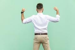 Ο συγκινημένος επιχειρηματίας γιορτάζει ένα επίτευγμα σταδιοδρομίας Πίσω άποψη ενός νέου ενήλικου επιχειρηματία, στο ανοικτό πράσ στοκ φωτογραφία