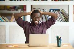 Ο συγκινημένος μαύρος εργαζόμενος ευχαριστημένος από τη λαχειοφόρο αγορά κερδίζει στοκ φωτογραφία με δικαίωμα ελεύθερης χρήσης