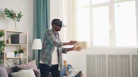 Ο συγκινημένος νεαρός άνδρας παίζει το παιχνίδι που φορά τα γυαλιά εικονικής πραγματικότητας που κινούν στο σπίτι τα όπλα και το  απόθεμα βίντεο