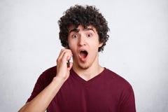 Ο συγκλονισμένος έφηβος κρατά το έξυπνο τηλέφωνο, μιλά με το φίλο, που τρομοκρατείται για να ακούσει τις κακές ειδήσεις, κρατά το στοκ εικόνες