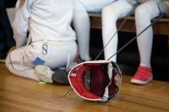 Ο συμμετέχων κοριτσιών στον ανταγωνισμό περίφραξης στα ξίφη κάθεται σε έναν πάγκο Στοκ Εικόνα
