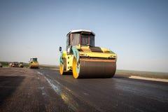 Ο συμπιεστής ασφάλτου του κίτρινου χρώματος με τους βαριούς συμπιεστές σιδήρου χτίζει το δρόμο Στοκ φωτογραφία με δικαίωμα ελεύθερης χρήσης