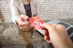 Ο συνάδελφος δίνει την κάρτα δώρων στη επιχειρηματία Στοκ εικόνα με δικαίωμα ελεύθερης χρήσης
