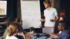 Ο συναισθηματικός επιχειρησιακός δάσκαλος παρουσιάζει για τους εταιρικούς σπουδαστές που μιλούν και που δείχνουν στο whiteboard ε απόθεμα βίντεο