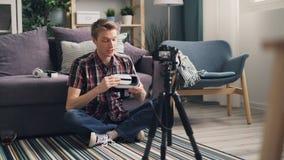 Ο συναισθηματικός νεαρός άνδρας blogger καταγράφει το βίντεο για τα γυαλιά εικονικής πραγματικότητας καθμένος στο πάτωμα που φορά φιλμ μικρού μήκους