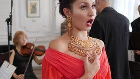Ο συναισθηματικός τραγουδιστής κινηματογραφήσεων σε πρώτο πλάνο στο κόσμημα και το κόκκινο φόρεμα τραγουδά στη συμφωνική ορχήστρα απόθεμα βίντεο