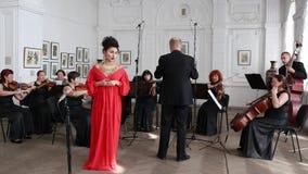 Ο συναισθηματικός τραγουδιστής σε ένα κόκκινο μακροχρόνιο φόρεμα και ένα ακριβό κόσμημα τραγουδά στο δωμάτιο ενάντια στο σκηνικό  φιλμ μικρού μήκους
