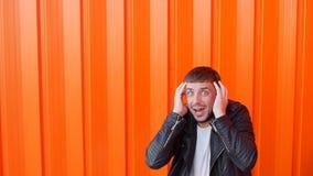Ο συναισθηματικός τύπος είναι έκπληκτος και εκμετάλλευση το κεφάλι του, φόβος, εκφράσεις του προσώπου, πορτοκαλί υπόβαθρο, σε αργ απόθεμα βίντεο