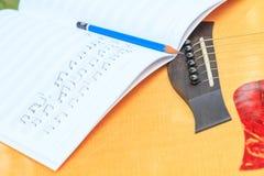 Ο συνθέτης γράφει τη σημείωση της ακουστικής κιθάρας τραγουδιού και χρήσης Στοκ Εικόνα