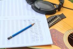 Ο συνθέτης γράφει τη σημείωση της ακουστικής κιθάρας τραγουδιού και χρήσης Στοκ φωτογραφία με δικαίωμα ελεύθερης χρήσης