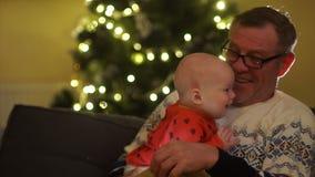 Ο συνταξιούχος ανοίγει ένα χριστουγεννιάτικο δώρο με το μικρό εγγονό του Τα φω'τα λάμπουν από το κιβώτιο, το μωρό κοιτάζει απόθεμα βίντεο