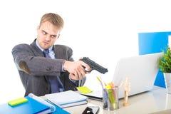 Ο συντριμμένος επιχειρηματίας ανέτρεψε μέσα το πυροβόλο όπλο εκμετάλλευσης έκφρασης προσώπου δείχνοντας τον υπολογιστή Στοκ Φωτογραφία