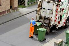 Ο συλλέκτης άχρηστων χαρτιών φορτώνει τα πράσινα εμπορευματοκιβώτια σε ένα φορτηγό στοκ φωτογραφίες με δικαίωμα ελεύθερης χρήσης