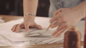 Ο σχεδιαστής επισύρει την προσοχή μια γραμμή σε χαρτί Σχεδιασμός και χρώμα γυναικών κλείστε επάνω απόθεμα βίντεο