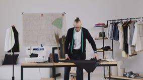 Ο σχεδιαστής και ο ράφτης ιματισμού εργάζονται με τις μετρήσεις σε έναν πίνακα στούντιο Κατασκευαστής των ενδυμάτων σε ένα ένδυμα απόθεμα βίντεο