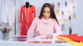 Ο σχεδιαστής κοριτσιών σύρει ένα σκίτσο του κόκκινου φορέματος για ένα περιοδικό μόδας νεολαίας απόθεμα βίντεο