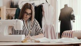 Ο σχεδιαστής μόδας, με ένα σοβαρό πρόσωπο, βάζει ένα σημάδι μολυβιών στο ύφασμα περιβάλλεται από μια ράβοντας μηχανή, α απόθεμα βίντεο