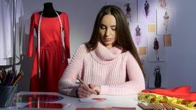 Ο σχεδιαστής μόδας σύρει ένα σκίτσο ενός κόκκινου φορέματος, εργαστήριο απόθεμα βίντεο