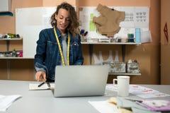 Ο σχεδιαστής των ενδυμάτων εργάζεται στο εργαστήριο μπροστά από το lap-top Στοκ φωτογραφία με δικαίωμα ελεύθερης χρήσης