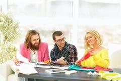 ο σχεδιαστής και η ομάδα του εργάζονται στα νέα μοντέλα στην ενδυμασία Στοκ Εικόνες