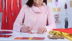 Ο σχεδιαστής κοριτσιών επισύρει την προσοχή ένα σκίτσο ενός φορέματος σε έναν πίνακα βρίσκεται δείγματα υφάσματος κλείστε επάνω απόθεμα βίντεο
