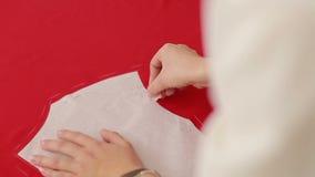 Ο σχεδιαστής μόδας επισύρει την προσοχή μια γραμμή στο ύφασμα Seamstress που απασχολείται στο σπίτι στο στούντιο απόθεμα βίντεο